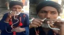 oldman pulling snake inside mouth and takr away from mouth